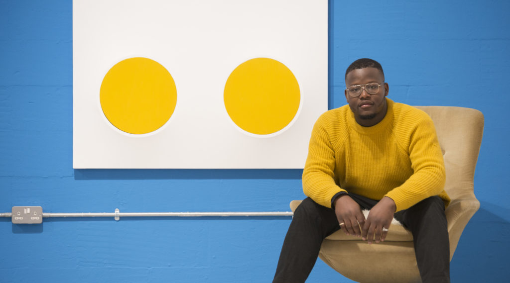 Jasper sat on a chair wearing a striking mustard jumper next to one of his works